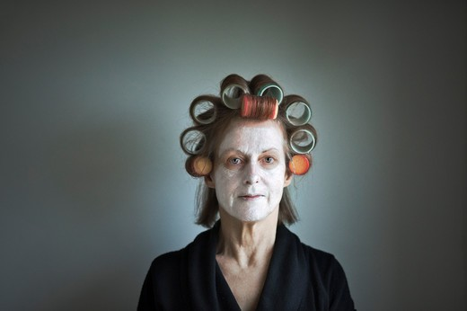 Stock Photo: 1236-175 Studio portrait of woman wearing large hair curlers and face mask