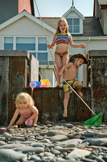 Stock Photo: 1236-185 United Kingdom, Wales, Three children with fishing nets in front of beach house