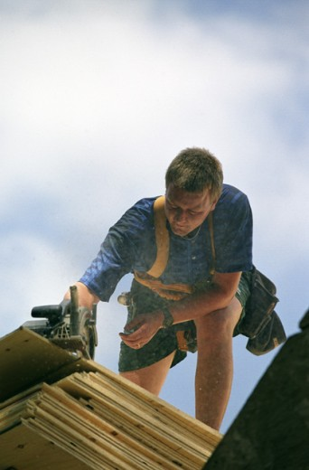 Low angle view of a carpenter cutting wood using an electric saw : Stock Photo