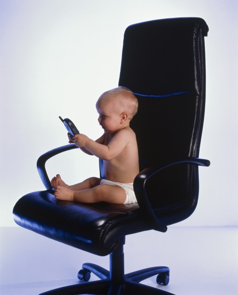 Stock Photo: 1244-4989 Baby sitting in an office chair and holding a mobile phone