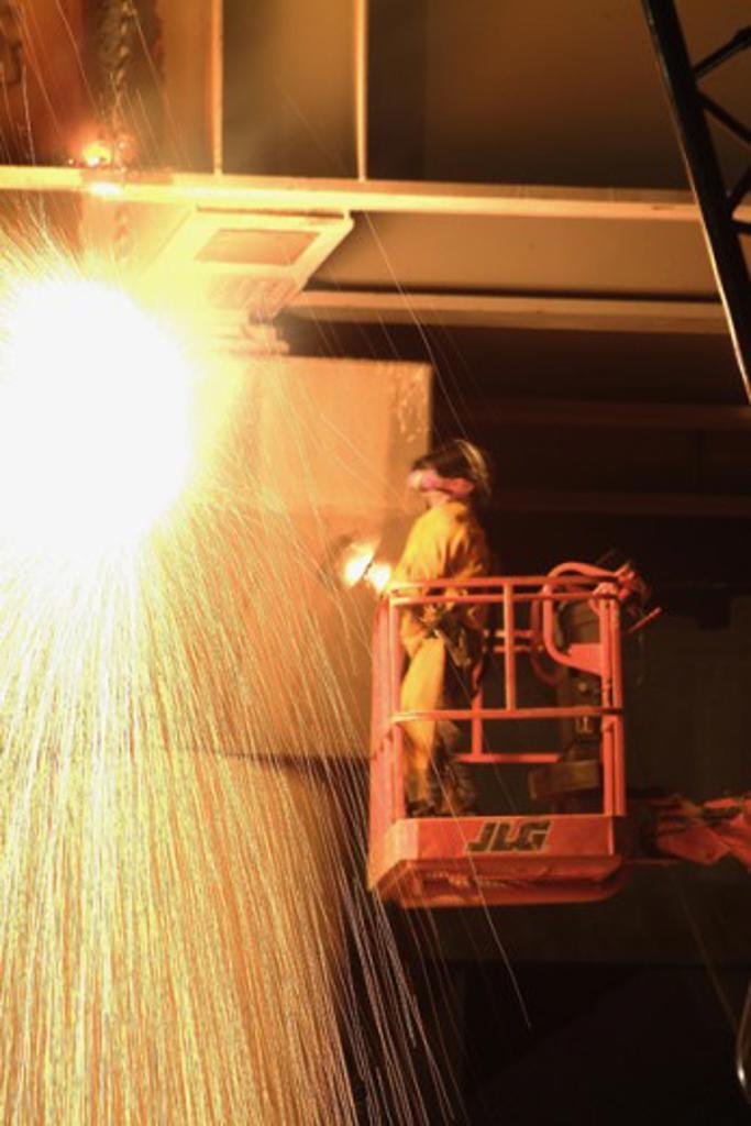 Stock Photo: 1245-458 A welder working on a bridge