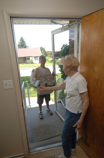 Senior woman receiving a newspaper from a paper delivery boy : Stock Photo