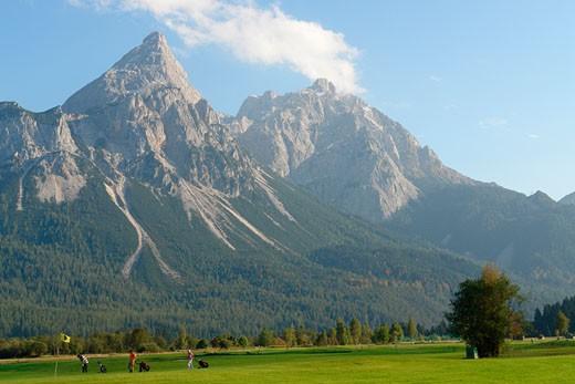 Golf course in front of mountains, Ehrwalder Sonnenspitze and Grunstein Mountains, Tyrol, Austria : Stock Photo