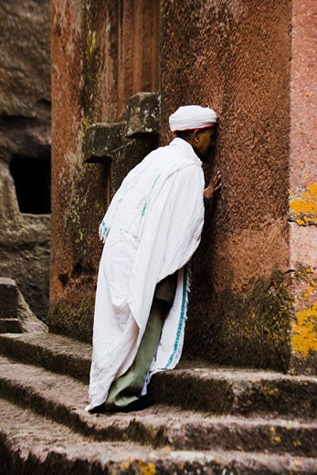 Stock Photo: 1269-2411A Priest praying in front of the wall of a church, St. George Church, Lalibela, Ethiopia