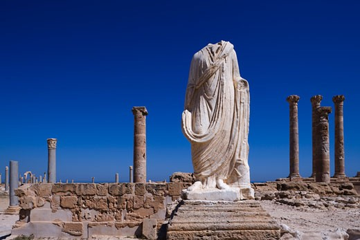 Headless statue with the ruins of buildings, Statue of Flavius Tullus, Sabratha, Tripolitania, Libya : Stock Photo