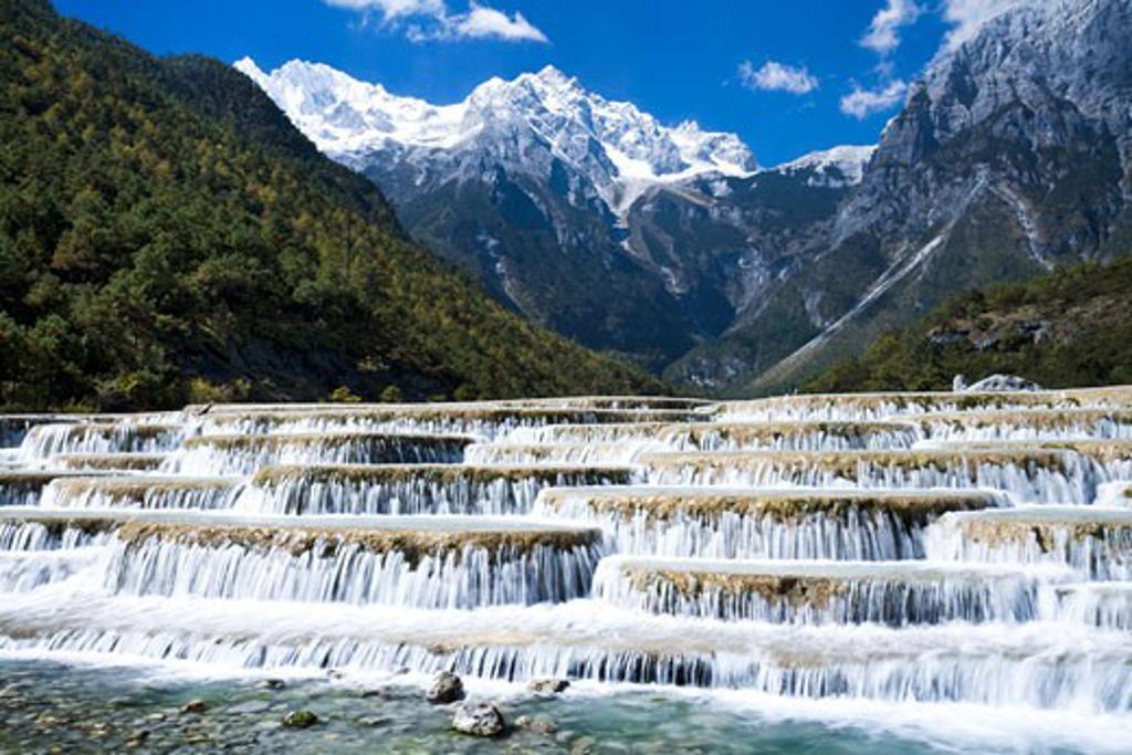 Stock Photo: 1269-3025A Cascading waterfall in front of a mountain range, Baishuitai Falls, Jade Dragon Snow Mountain, Lijiang, Yunnan Province, China