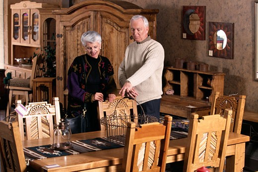 Stock Photo: 1284-444 Senior couple purchasing dining table in furniture shop,