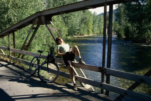 Young woman sitting on a bridge, Sun Valley, Idaho, USA : Stock Photo
