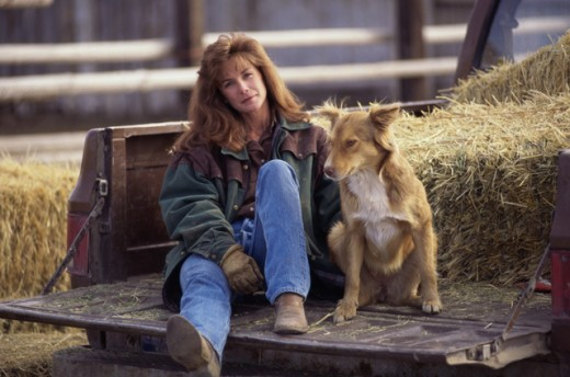 Stock Photo: 1284R-1038 Portrait of a woman sitting at the back of a pick-up truck with her dog