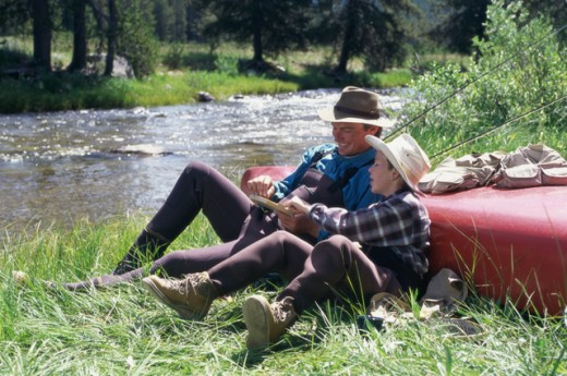 Father and son sitting by a river : Stock Photo