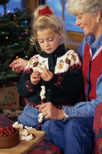 Stock Photo: 1284R-1174 Grandmother and granddaughter making a garland