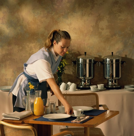 Stock Photo: 1284R-1447 Waitress laying a table