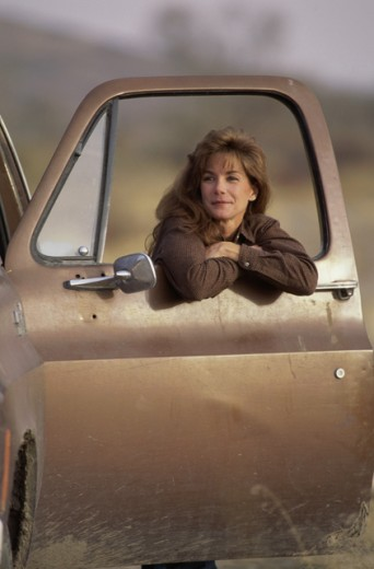 Stock Photo: 1284R-1454 Portrait of a young woman leaning against an open car door