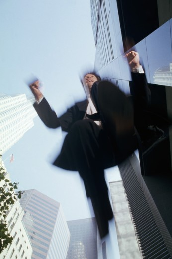 Low angle view of a businessman jumping : Stock Photo