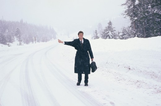 Stock Photo: 1284R-1563 Businessman standing on a snow covered road hitchhiking