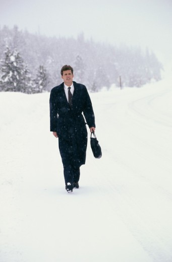 Businessman walking on a snow covered road : Stock Photo