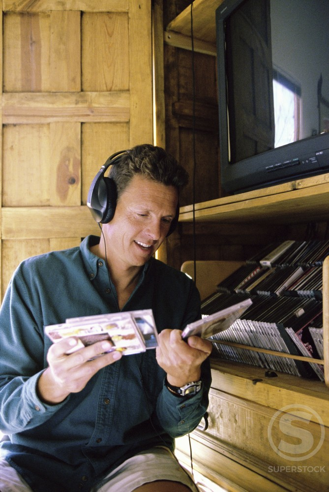 Mid adult man wearing headphones and holding CD's : Stock Photo