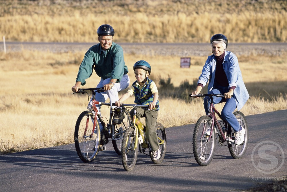 Stock Photo: 1284R-256 Grandparents riding bicycles with their grandson