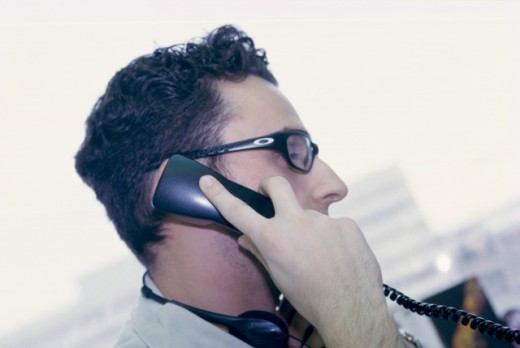 Side profile of a businessman talking on a telephone : Stock Photo