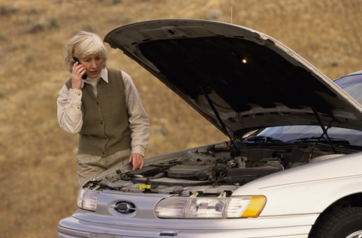 Senior woman standing near a broken down car talking on a mobile phone : Stock Photo