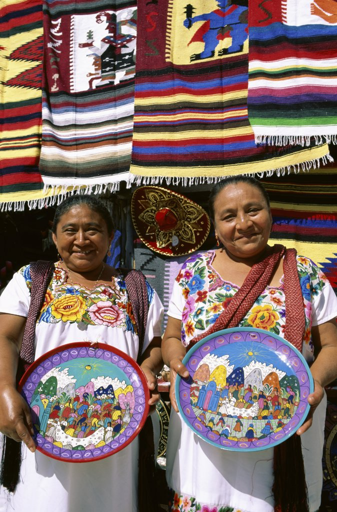 Stock Photo: 1288-1081 Portrait of two mature women holding decorated plates, Cancun, Mexico