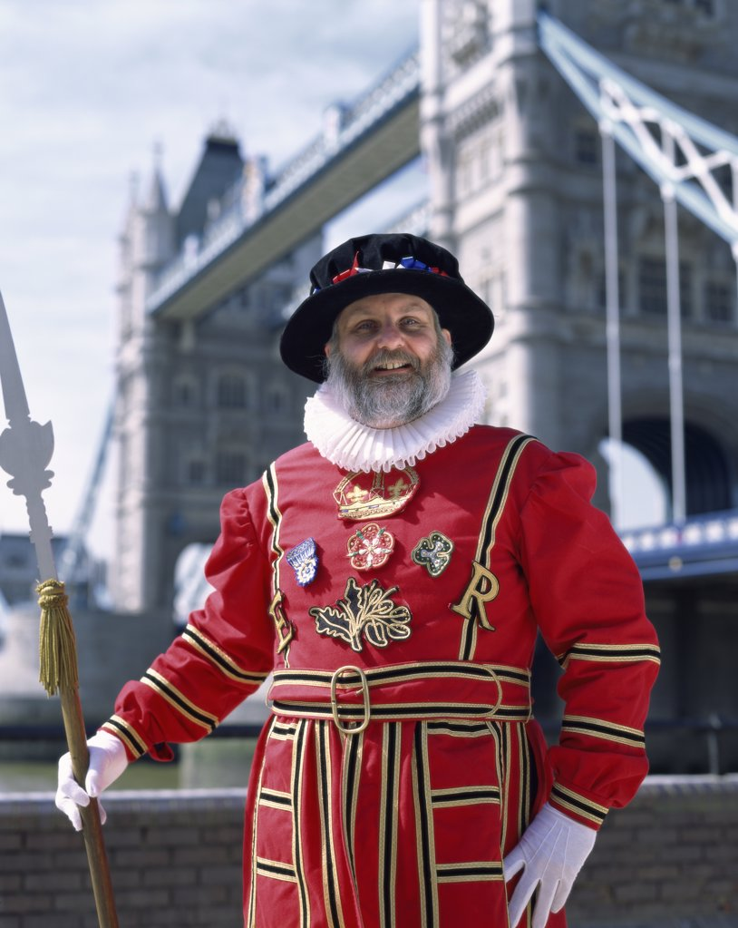 Portrait of a Beefeater standing with a bridge in the background, Tower Bridge, London, England : Stock Photo