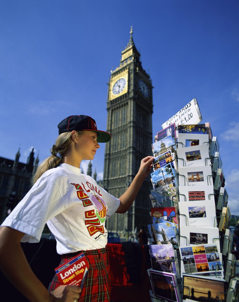 Side profile of a young woman choosing postcards with a clock tower in the background, Big Ben, London, England : Stock Photo