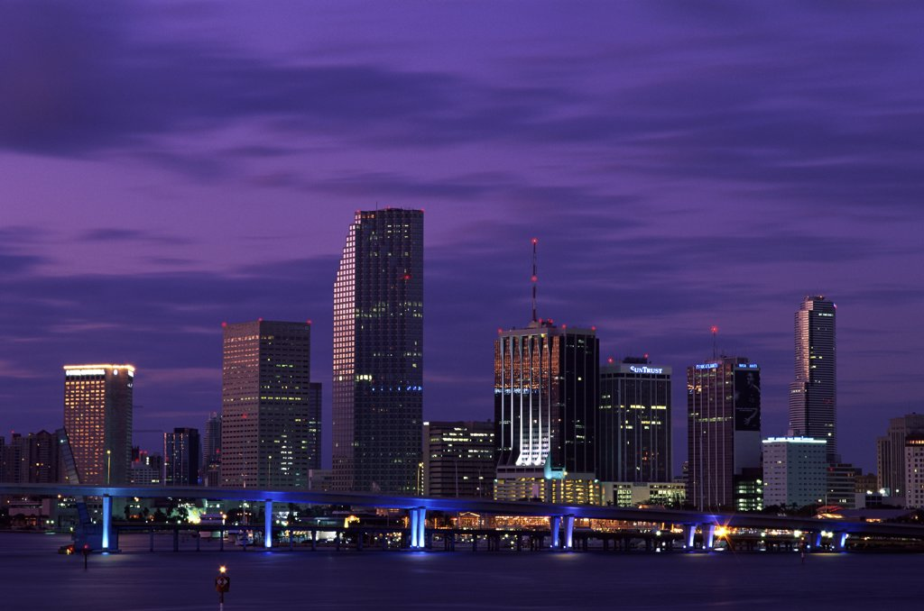 Buildings on the waterfront lit up at dusk, Miami, Florida, USA : Stock Photo