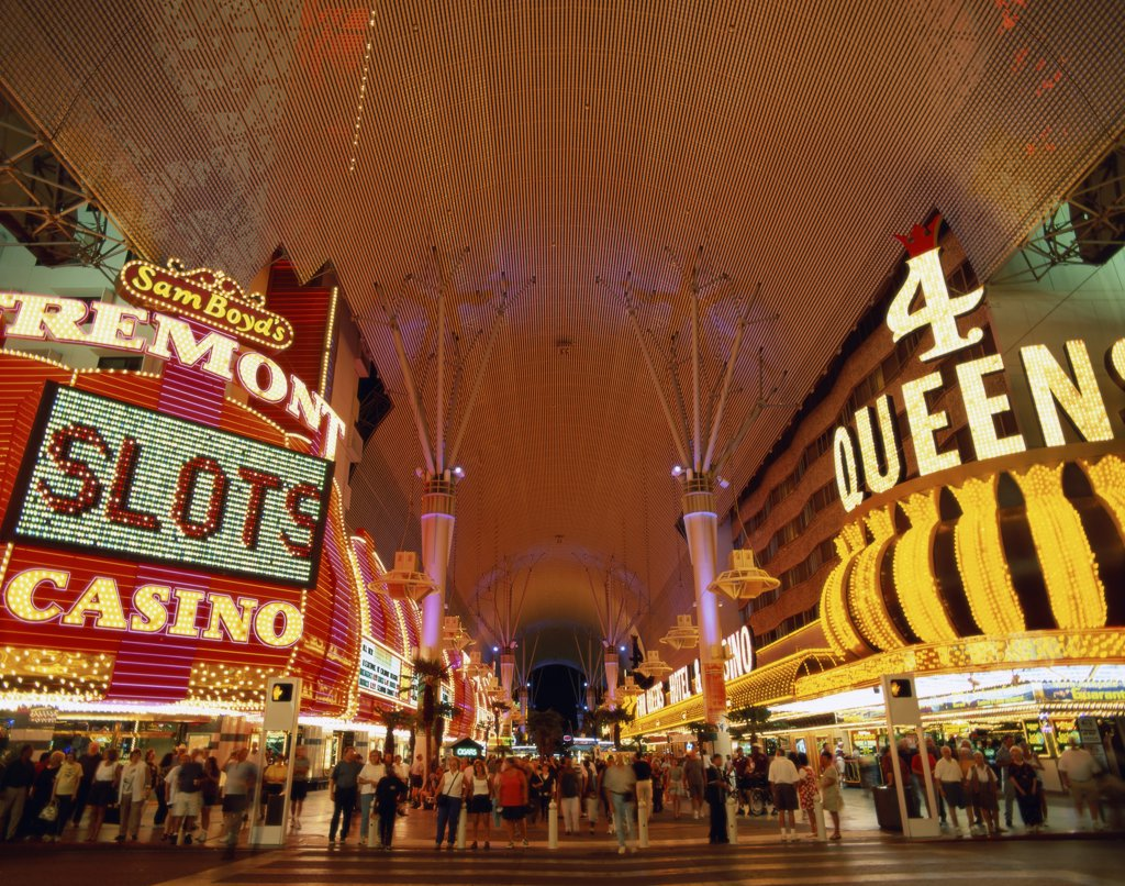 Tourists at a casino lit up at night, Fremont Street, Las Vegas, Nevada, USA : Stock Photo