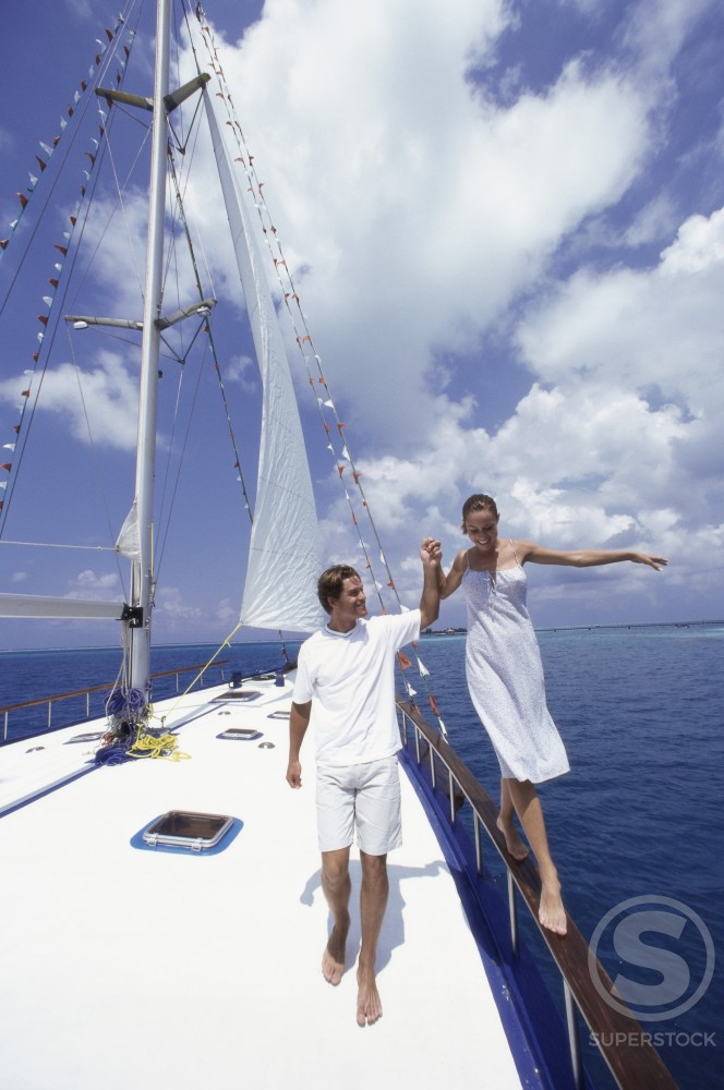 Young woman walking on a railing of a sailboat with a young man holding her hand : Stock Photo