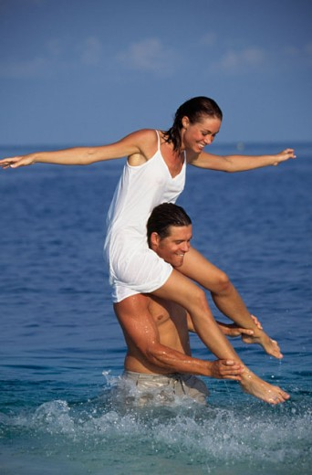 Young man standing in water carrying a young woman on his shoulders : Stock Photo