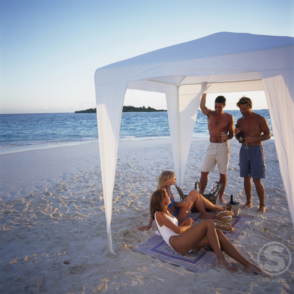 Stock Photo: 1290-126B Two young couples under a tent on the beach