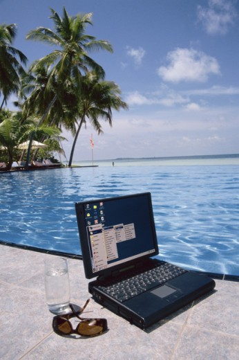 Stock Photo: 1290-138 Close-up of a laptop and sunglasses at poolside