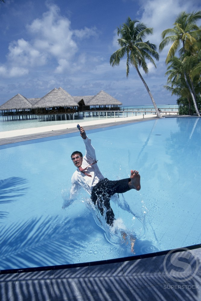 Stock Photo: 1290-142B Businessman falling in a swimming pool with a mobile phone