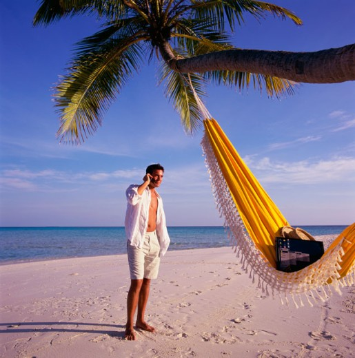 Young man standing on the beach talking on a mobile phone, Maldives : Stock Photo