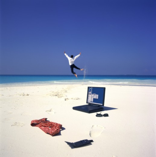 Stock Photo: 1290-184A Laptop and a mobile phone on the beach with a businessman jumping in the background