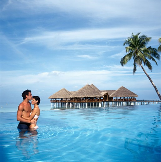 Side profile of a young couple standing in water and embracing each other, Maldives : Stock Photo