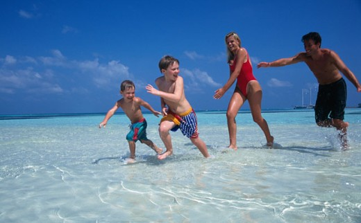 Stock Photo: 1290-261B Young couple with their two sons running on the beach