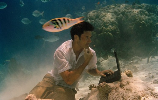 Young man sitting underwater and using a laptop : Stock Photo