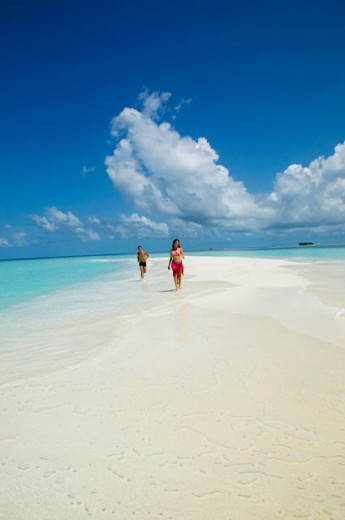 Young couple running on the beach, Maayafushi, Maldives : Stock Photo