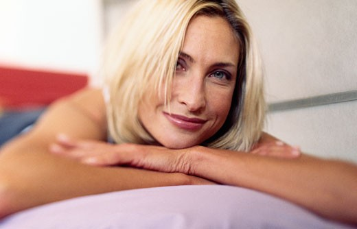 Stock Photo: 1295-328A Portrait of young woman lying on front, looking at camera and smiling