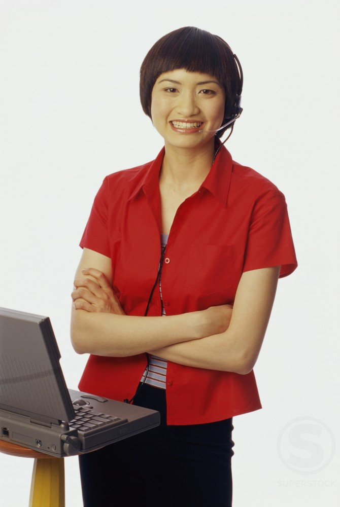 Portrait of a young woman standing in front of a laptop : Stock Photo