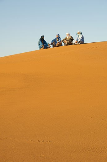 Stock Photo: 1301-571B Tuareg men sitting in a desert, Sahara Desert, Merzouga, Morocco