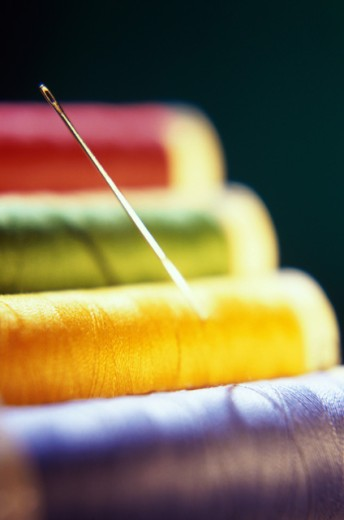 Close-up of a needle on spools of colored thread : Stock Photo