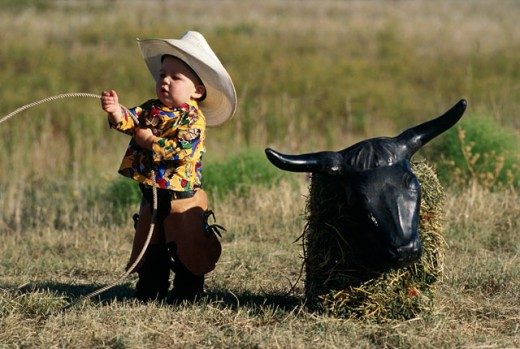 Boy dressed as a cowboy holding a lasso : Stock Photo