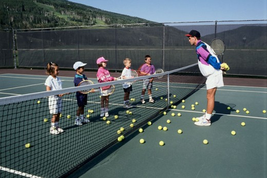 Boys and girls with their coach on a tennis court : Stock Photo