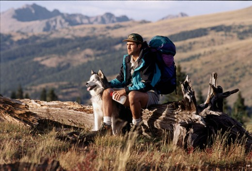 Stock Photo: 1308-460 Young man sitting on a log with his dog, Vail, Colorado, USA