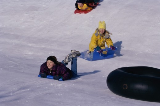 Two girls and a boy sledding on snow : Stock Photo