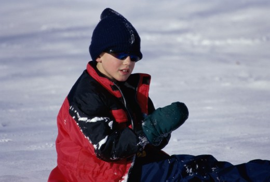 Boy sitting in snow : Stock Photo