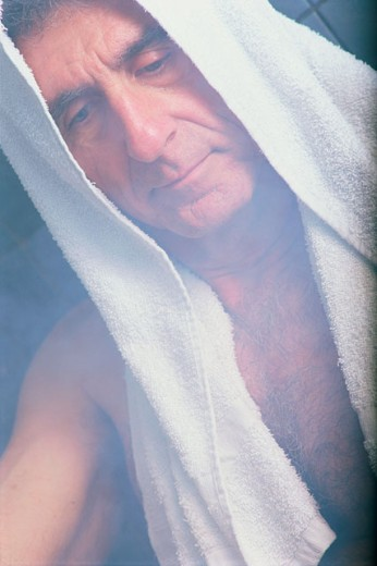 Close-up of senior man with a towel around his head looking down : Stock Photo